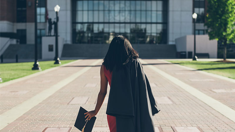 Recent graduate walking towards building